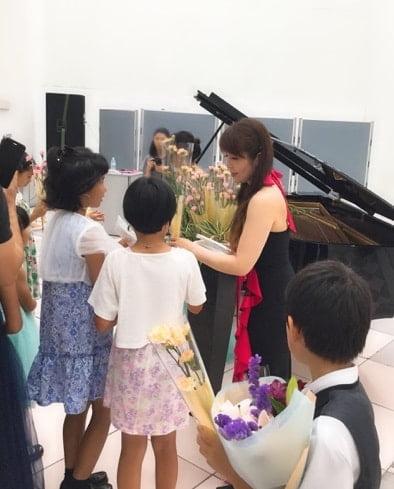 講師がピアノ演奏の後に、生徒たちに花を配る写真